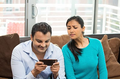 couple on couch, man distracted by phone